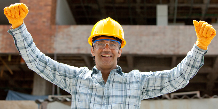successful_enginee_smiling_with_arms_up_at_construction_site